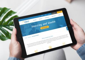 Hands holding a tablet showing the Libro website