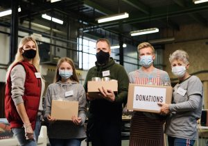 Non-profit volunteers hold up packages