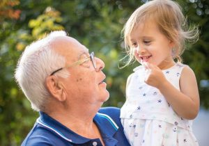Grandparent holds child up high while in the garden